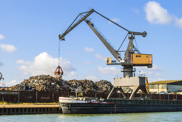 Harbor - crane loading a ship with scrap metal