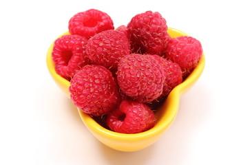 Fresh raspberries in yellow bowl on white background