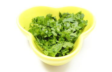 Fresh and natural chopped parsley in yellow dish.
