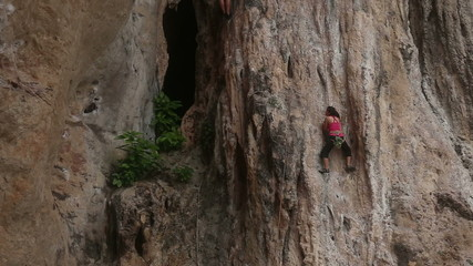 climber climbing a cliff with insurance