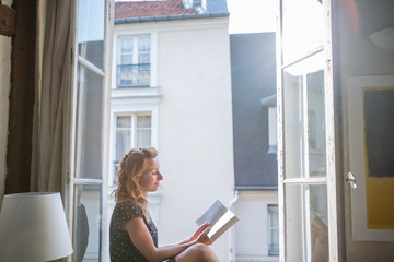 Woman reading a book by the window