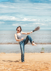 Funny woman with broom on the beach