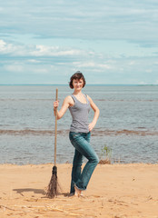Woman with broom on the beach