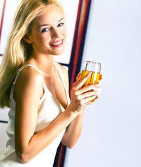 Young attractive blond woman with glass of juice