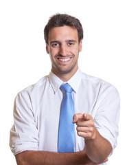 Geschäftsmann mit blauer Krawatte zeigt zur Kamera