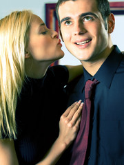 Young attractive smiling couple or business people kissing