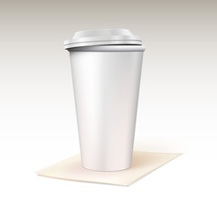 Paper cup for coffee standing on a napkin.
