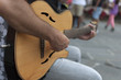 artista di strada con chitarra, con pubblico sullo sfondo