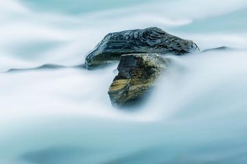 Bach mit fließendem Wasser und Steinen