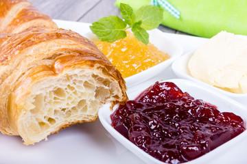 Croissant zum Frühstück mit Marmelade und Butter