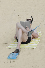Man in flippers reads book