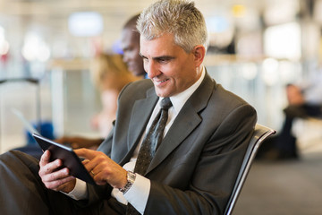senior businessman using tablet computer at airport