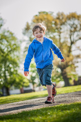 Boy running and laughing in the park.