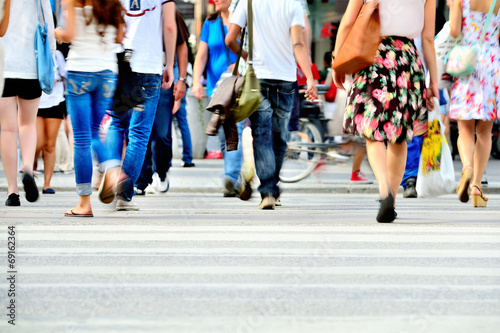 Leinwanddruck Bild Motion blurred pedestrians crossing sunlit street