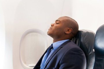 african businessman resting on airplane