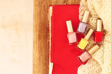 top view of nail polish bottles over wooden table. filtered imag