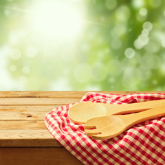 Wooden spoon on tablecloth over garden bokeh background