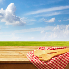 Wooden table with kitchen utensil over green meadow and blue sky