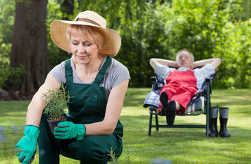 Woman planting flowers and resting man