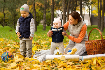 young mother with her children in the park autumn