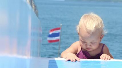 baby crawls deck ship ocean