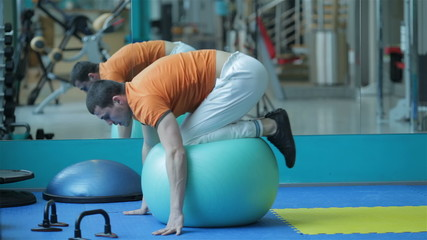 young man in a red shirt doing exercise on fit-ball for abdomina