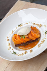 Apricots, biscuit and vanilla ice cream on a plate
