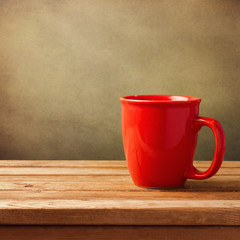 Coffee cup on wooden table over grunge background