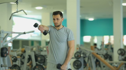 young man doing exercise with dumbbells for triceps