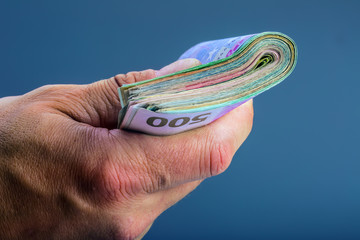 Hand with money, a few hundred euros in banknotes