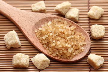 Brown cane sugar crystals in a wooden spoon