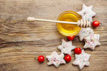 Gingerbread christmas cookies and bowl of honey on wooden table