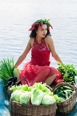 elegant woman with vegetables in a boat on the water