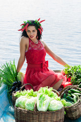 cute woman with vegetables in a boat on the water