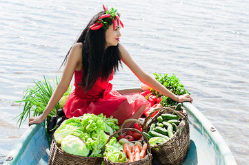 smiling woman with vegetables in a boat on the water