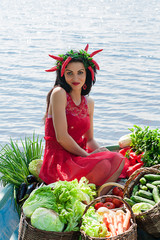 funny woman with vegetables in a boat on the water