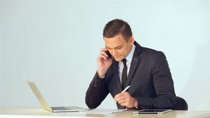 young businessman making notes in a notebook talking