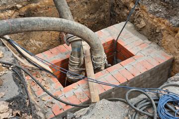 Grosse Pumpenschläuche führen in einen gemauerten Abwasserkanal