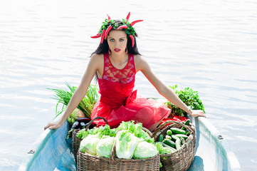 beautiful woman with vegetables in a boat on the water