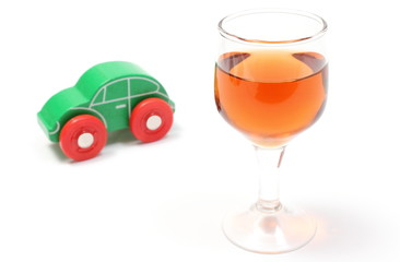 Glass of wine and wooden toy car. White background