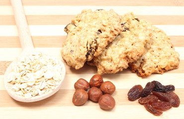 Oatmeal cookies with raisins and hazelnut on wooden background