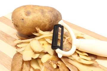Potato with peels and peeler lying on wooden cutting board
