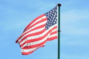 American flag flying in Blue sky