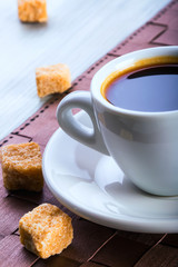Cup of black coffee with a few cubes of cane sugar