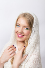 Beautiful blonde girl in a white shawl