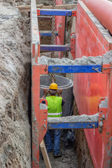 Worker setting concrete pipe in trench