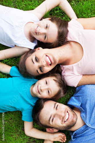 canvas print picture Family outdoors lying on grass