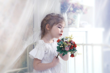 cute little girl with a bouquet in her hands in the bedroom