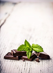 A few cubes of black chocolate with mint leaves on wooden table