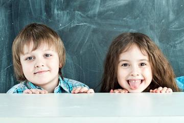 Boy and girl hiding behind a table near the school board